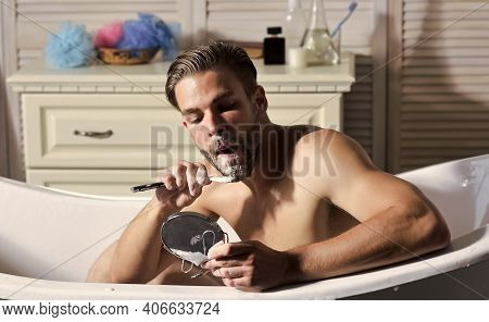 Bearded Man Shave Beard With Razor In Bathtub In Bathroom. Bearded Man With Shaving Soap On Beard Lo