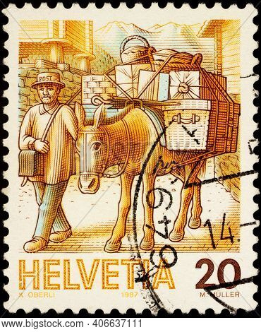 Moscow, Russia - February 03, 2021: Stamp Printed In Switzerland Shows Post By Mule, Man Leads A Mul