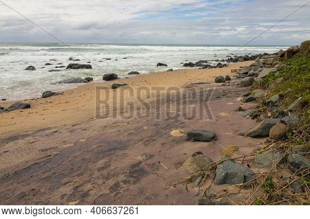 Stretch Of Wet Beach And Rocks With Ebbing Tide