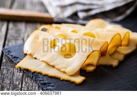 Sliced smoked hard cheese on cutting board.