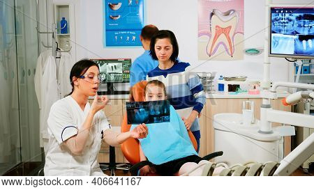 Stomatologist Explaining Dental Treatment Holding Radiography Pointing On Affected Teeth While Man A