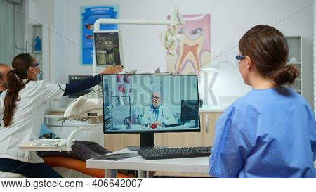 Nurse Discussing About Consultation With Senior Dentist Medic On Video Call In Dental Office, While