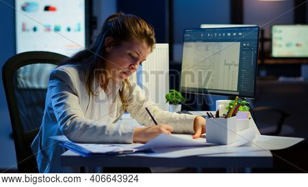 Overworked Woman Architect Analysing And Matching Blueprints Sitting At Desk In Front Of Computer La