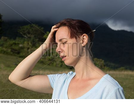 Woman With Headache On Sky Storm Background. A Woman With A Headache On Natural Background. A Woman