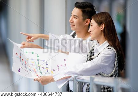 Close-up Side View Portrait Of Cute Smiling Young Asian Couple Tourists Standing And Holding Paper M