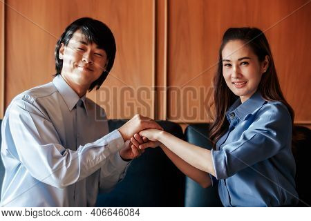 Asian Christian Woman And Man Smiling Join Hands In Praying For Jesus' Blessings To Show Love And Co
