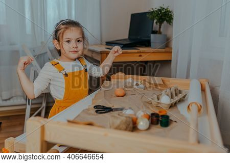Baby Girl Decorating Easter Eggs On White Table. Kid Decorating Eggs With Kraft Paper, Lace And Rope