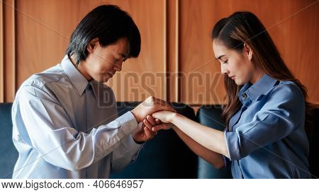 Asian Christian Woman And Man Join Hands In Praying For Jesus' Blessings To Show Love And Confession
