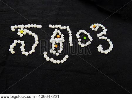 Written As Sankranti In Kannada Or Pongal Using Sugar Coated White Balls Isolated On Black Backgroun