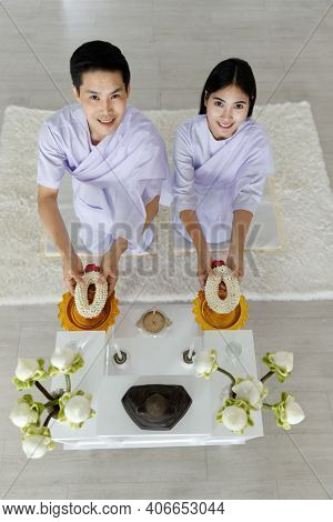 Man And Woman Buddhist In White Dress Sitting In Front Of Set Of The Altar Table And Giving Fresh Ga