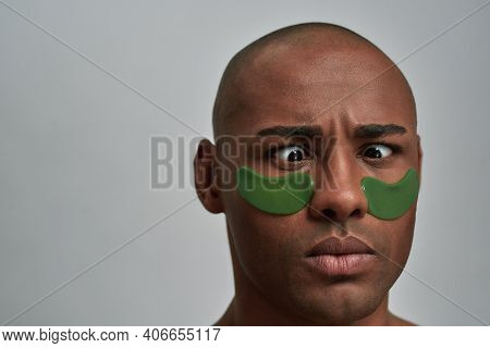 Man Making Goofy Facial Expression And Keeping Eyes On The Nose With Skin Care Masks Under Them