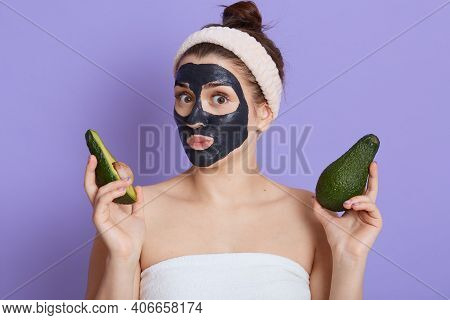 Cute Young Woman Wrapped In Towel Looking Directly At Camera, Holding Half Of Fresh Ripe Avocado, Ma
