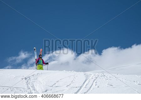 A Young Woman In Ski Equipment Stands In The Middle Of A Snowy Field In The Mountains Against A Back