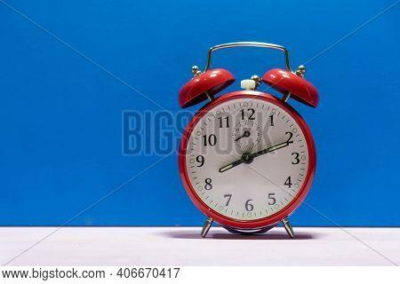 Red Color Mechanical Alarm Clock On Blue Background