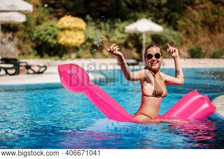 Sexy Woman In Sunglasses With A Smile On Her Face In A Swimsuit Lies On A Pink Inflatable Mattress I