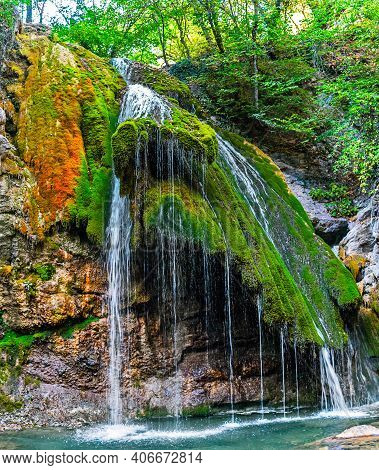 Beautiful Waterfall Among The Forest In The Mountains