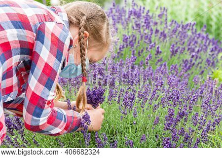 Little Girl With Allergy . Child In A Mask Holds Lavender Flowers