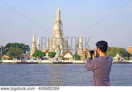 Man Taking Photos Of The Temple Of Dawn Or Wat Arun, The Iconic Landmark Located On Chao Phraya Rive