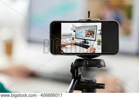 technology, post production and vlog concept - smartphone recording process of woman working in video editor program on laptop computer at home office