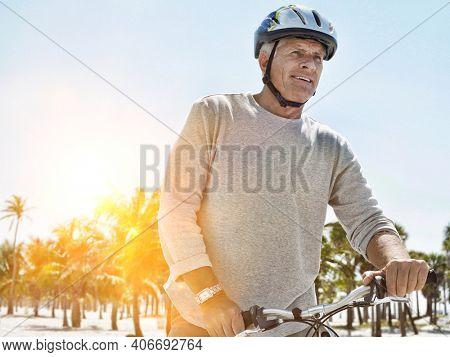 Senior man wearing helmet riding bicycle on tropical beach