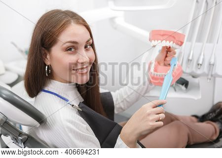 Cheerful Female Patient Smiling, Holding Dental Model And Toothbrush At Dental Chair