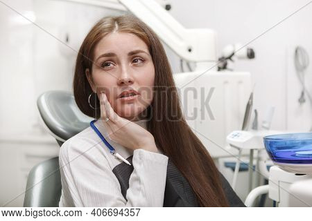 Close Up Of A Woman Suffering From Toothache, Sitting In Dental Chair At The Clinic