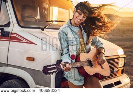 Hipster Beautiful Woman Playing Guitar With Big Smile On Her Face. Nomadic And Camper Lifestyle Conc