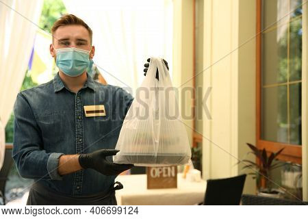 Waiter With Packed Takeout Order In Restaurant. Food Service During Coronavirus Quarantine