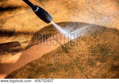 Defocused Image. Cleaning Backyard Paving Tiles Pathway With High Pressure Washer. Spring Clean Up