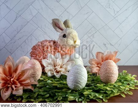Easter Rabbit Bunny Sitting On A Bed Of Green Leaves With Peach Dahlia Flower Blooms And String Deco