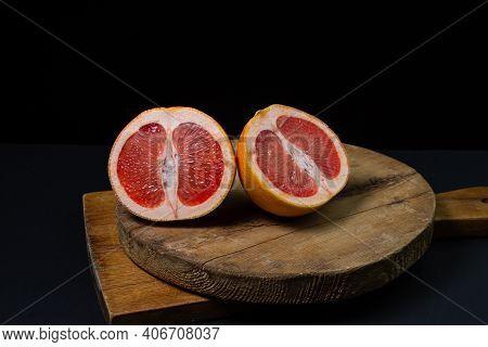 Grapefruit On A Black Background. Grapefruit Cut In Half On A Wooden Board. Citrus Fruit. Exotic Fru