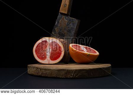 Grapefruit On A Black Background. A Grapefruit Cut In Half With An Ax. Citrus Fruit. Exotic Fruit
