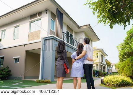 Asian Woman Real Estate Broker Agent Showing A House Detail In Her File To The Young Asian Couple Lo