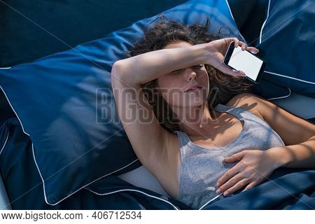 Top view of young woman sleeping in bed while holding mobile phone. Girl sleeping in blue linen with smart phone. Woman lying in bed fell asleep while texting meassage with smartphone late in night.