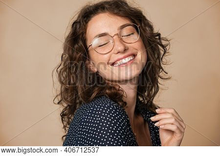 Casual cheerful woman with eyeglasses smiling at camera on cream background. Close up of happy young woman laughing with eyeglasses. Beautiful girl having fun with closed eyes showing a big grin.