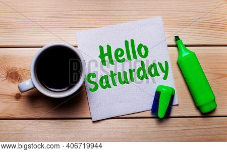 On A Wooden Table, A Cup Of Coffee, A Green Marker And A Napkin With The Text Hello Saturday