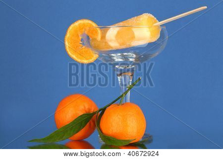 Yellow fruit juice ice in vase on blue background