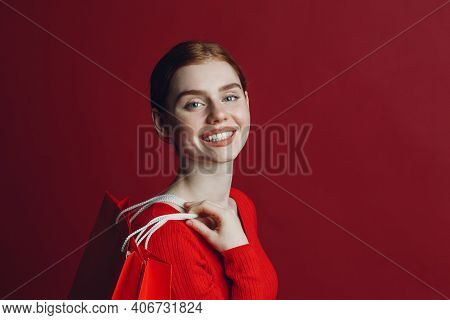 Pretty Woman Smilng Portrait With Paper Red Shopping Bags. Black Friday And Sale Concept.