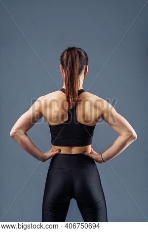 Pumped Up Strong Fitness Sportswoman Showing Back And Biceps Muscles Strength. Fit Girl Fitness Mode