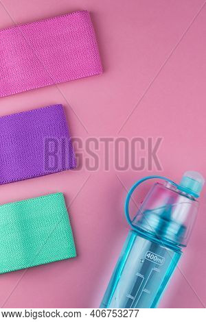 Colorful Fitness Gums On Pink Background. Elastic Expanders And Tapes Of Different Color. Colored Ru
