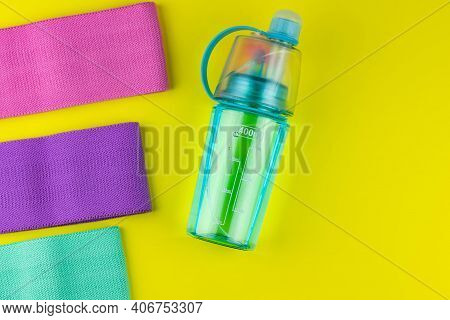 Colorful Fitness Gums On Yellow Background. Elastic Expanders And Tapes Of Different Color. Colored