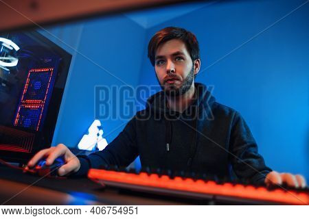 Portrait Of Professional Young Gamer Playing Online On His Modern Pc. He Is Serious And Focused On G