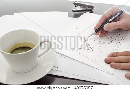Holding A Pen Over A Business Document