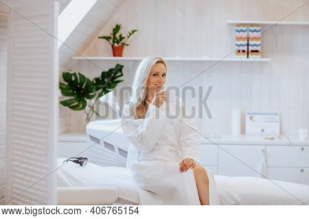 Young Pretty Blond Woman In White Bathrobe Posing With Cup Of Coffee In A Hair Removal Cabinet.