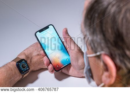 Morgantown, Wv - 5 February 2021: Apple Iphone And Watch Use Face Recognition To Open Phone Even Whe