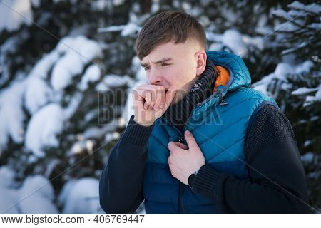 Sick Ill Guy, Young Man Coughing In His Fist, Hand, Suffering From Cough, Bronchitis At Cold Snowy W