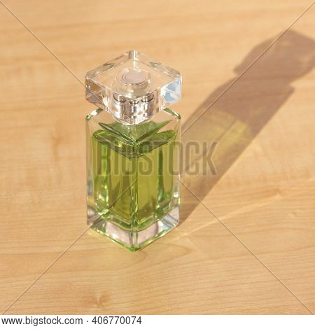 Close-up Of Glass Bottle With Scented Perfume On Wooden Table. Luxury Odor Presented In Fragile Vess