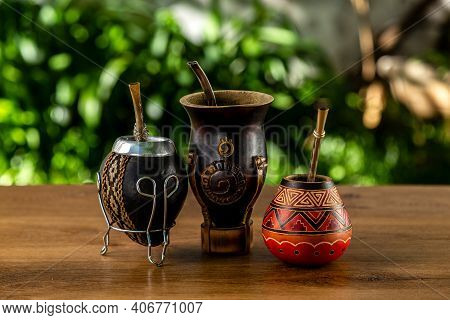 Three Traditional Mates Made Of Calabash Over A Wooden Table Outdoors. Culture Of South America.