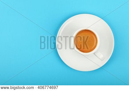 Close Up One White Cup Full Of Espresso Coffee On Saucer Over Blue Background, Elevated Top View, Di