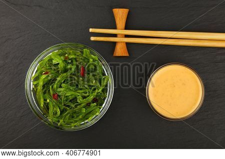Close Up Bowl Of Green Wakame Seaweed Salad With Satay Sauce And Chopsticks On Black Slate Board Bac